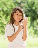 Smart telefon för Asien flickabruk i trädgård Royaltyfria Bilder