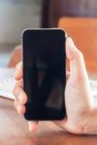 Smart telefon i en kvinnas hand Arkivbild