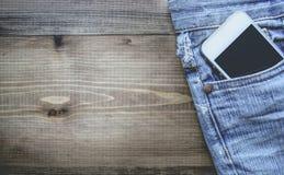 Smart telefon i fick- gamla Jean på träbakgrund med kopieringsSp Royaltyfri Bild