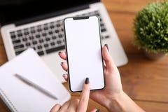 Smart telefon i hand på bakgrunden av den arbetande affärsmiljön, tom skärm arkivbild