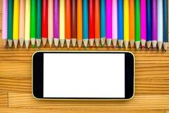 Smart telefon med blyertspennor på tabellen Arkivfoto