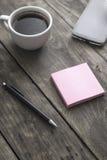 Smart telefon med den klibbiga anmärkningspapper och koppen kaffe Fotografering för Bildbyråer