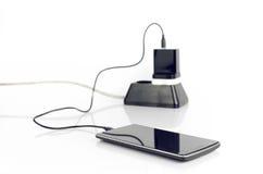 Smart telefon med den pluggade uppladdaren Arkivfoto