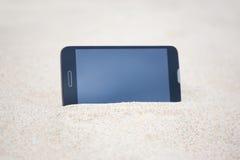 Smart telefon med den tomma skärmen i sand Arkivfoton