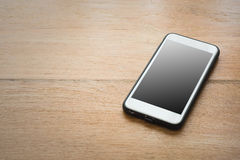 Smart telefon med den tomma skärmen på wood bakgrund Arkivbilder