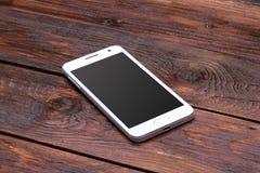 Smart telefon med den tomma skärmen som ligger på trä Arkivbild