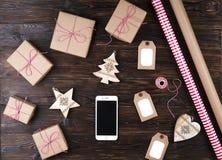 Smart telefon med julgåvor på bästa sikt för träbakgrund Online-ferieshoppingbegrepp Lekmanna- lägenhet, textutrymme Internet Arkivfoton