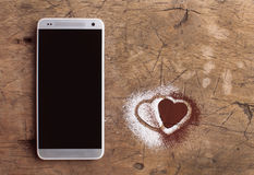 Smart telefon och hjärtor av socker och kakao Arkivfoto