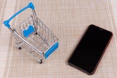 Smart telefon och shoppingvagn på modellbakgrund royaltyfri foto