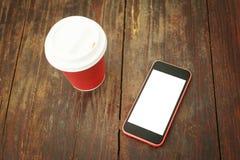 Smart telefon och takeaway kaffekopp på trätabellen Royaltyfria Bilder