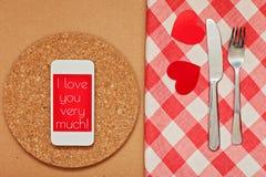 Smart telefon på köksbordet med gaffeln och kniven för en förklaring av förälskelse Arkivbild