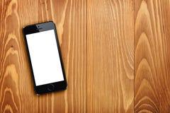 Smart telefon på trätabellen arkivfoto