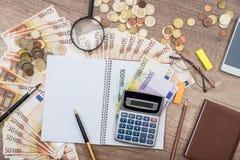 Smart telefon, penna, europengar med notepaden, penna, räknemaskin på kontoret Fotografering för Bildbyråer