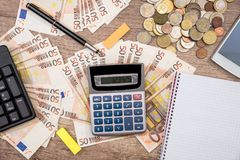 Smart telefon, penna, europengar med notepaden, penna, räknemaskin på kontoret Arkivbild
