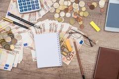 Smart telefon, penna, europengar med notepaden, penna, räknemaskin på kontoret Arkivfoto