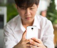 Smart telefoninnehav av den unga mannen Fotografering för Bildbyråer