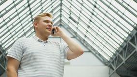 Smart telefonman som kallar på mobiltelefonen på natten i stad Stilig ung affärsman som talar på att le för smartphone stock video