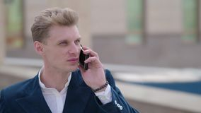 Smart telefonman som kallar på mobiltelefonen på natten i stad Stilig ung affärsman som talar på att le för smartphone arkivfilmer