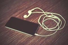 Smart telefonmobiltelefon och hörlurar Fotografering för Bildbyråer