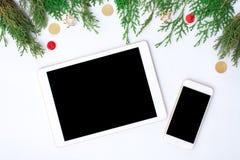 Smart telefonskärm för minnestavla på tabellen på den vita skärmen för modell i jultid Julgran garneringar Royaltyfri Bild
