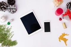 Smart telefonskärm för minnestavla på tabellen på den vita skärmen för modell i jultid Julgran garneringar i bakgrund arkivfoto