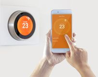 Free Smart Thermostat And A Person Setting Up The Temperature Smart Device Hand Hold On A White Background Stock Images - 165171784