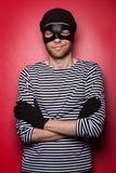 Smart thief. Classic thief standing at the red background Royalty Free Stock Images