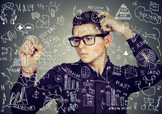 Smart thoughtful guy writing maths and science formulas on blackboard royalty free stock images