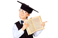 Smart thoughts. Portrait of a smart schoolboy in a suit and academic hat standing with opened book. Education. Isolated over white Royalty Free Stock Image