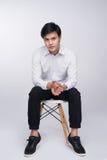 Smart tillfällig asiatisk man som placeras på stol som poserar, medan se royaltyfri fotografi