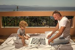 Smart toddler concept. Dad with child play intellectual game. Parent play chess with kid on terrace on sunny day. Father. And little son play chess on balcony Royalty Free Stock Image