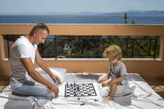 Smart toddler concept Dad with child play intellectual game Father and little son play chess on balcony nature and sea. Smart toddler concept Dad with child play Royalty Free Stock Photography