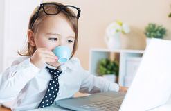 Smart toddler girl with glasses drinking coffee while using a laptop Royalty Free Stock Photography