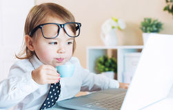 Smart toddler girl with glasses drinking coffee while using a laptop Royalty Free Stock Image