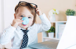 Smart toddler girl with glasses drinking coffee while using a laptop Royalty Free Stock Photo