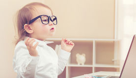 Smart toddler girl wearing big glasses using her laptop Stock Images