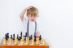 Smart toddler learning to play chess Stock Images