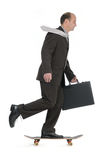 Smart transportation. Relaxed Businessman speeding with skateboard Stock Photography