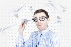Smart travelling business man throwing paper plane. In amongst a flurry of aeroplanes in departure and arrival Stock Image