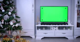 Smart tv with green screen near Christmas tree in living room