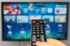 Smart tv and hand hold  remote control Stock Photos