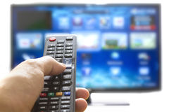 Smart tv and hand pressing remote control. Television remote control changes channels thumb on the blue TV screen Stock Photo