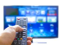 Smart tv and hand pressing remote control Royalty Free Stock Images