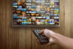 Smart tv and hand pressing remote control Royalty Free Stock Photography