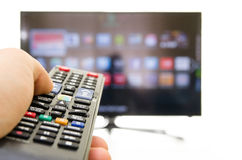 Smart tv and hand pressing remote control Stock Images
