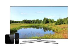 Smart tv and multimedia box with remote controller and landscape wallpaper on screen Stock Image