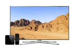 Smart tv and multimedia box with remote controller and mountain landscape wallpaper on screen Royalty Free Stock Photo