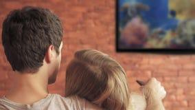 Smart tv och trängande fjärrkontroll för par arkivfilmer
