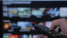 Smart TV Online-video strömmande service med apps och handen Den manliga handen som rymmer fjärrkontroll, vänder av livsstil smar arkivfilmer