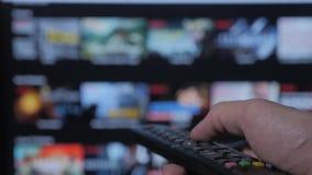 Smart TV Online-video strömmande service med apps och handen Manliga det avlägsna handinnehavet kontrollen vänder av smart tv stock video
